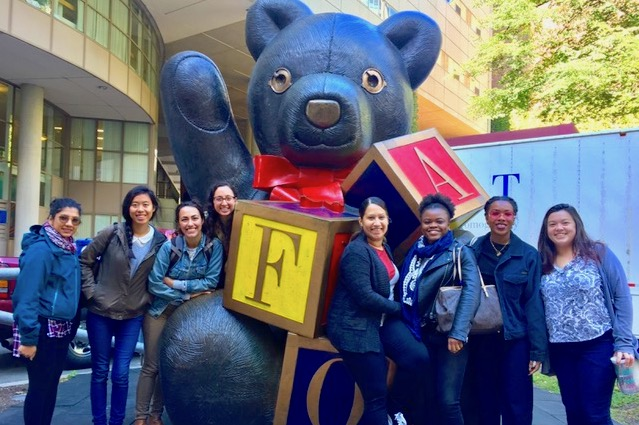 Fellows pose with the FAO Schwarz toy store bear